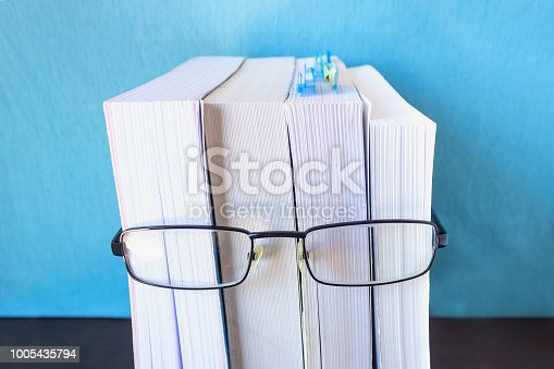 A stack of thick new books and black glasses  depict a person's face. Concept- reading, preparation for exams, training. Selective focus.