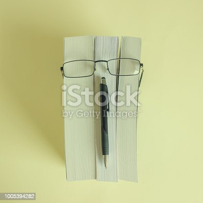 A stack of thick new books, glasses and a pencil depict a person's face. Concept- reading, preparation for exams, training. Selective focus.