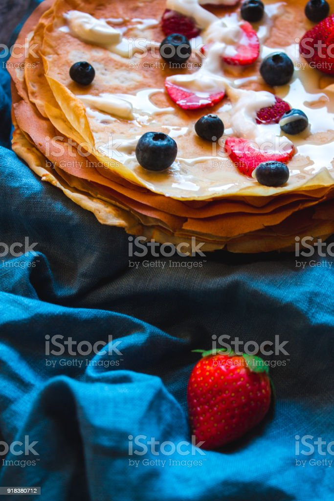 Stack of thin pancakes decorated with fresh strawberries and blueberries. The concept of Russian holiday Maslenitsa, Shrovetide stock photo