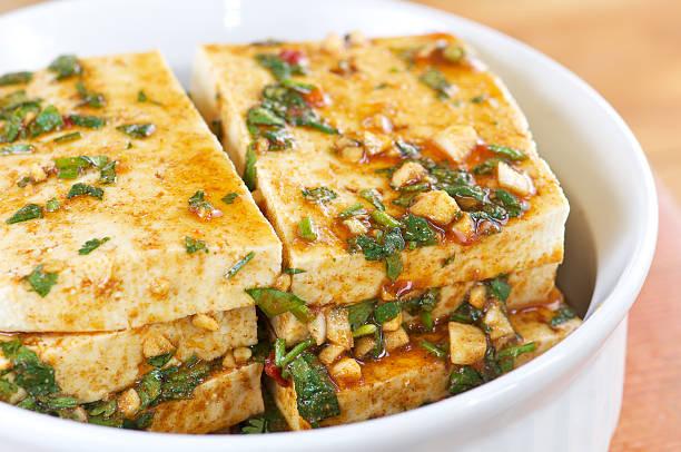 stapel von tofu scheiben mariniert in weiß schüssel - mariniertes tofu stock-fotos und bilder