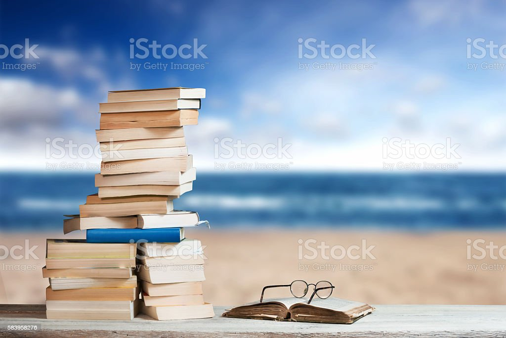 Stack of Travel Guides before a empty Beach stock photo