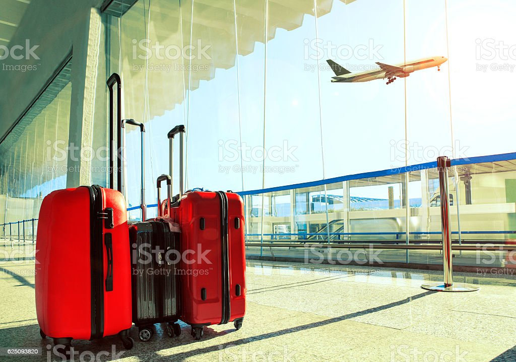 stack of traveling luggage in airport terminal and passenger pla stock photo