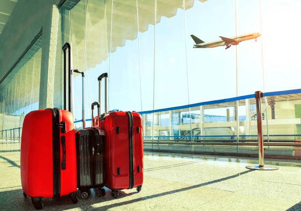 stack of traveling luggage in airport terminal and passenger plane flying over sky stock photo