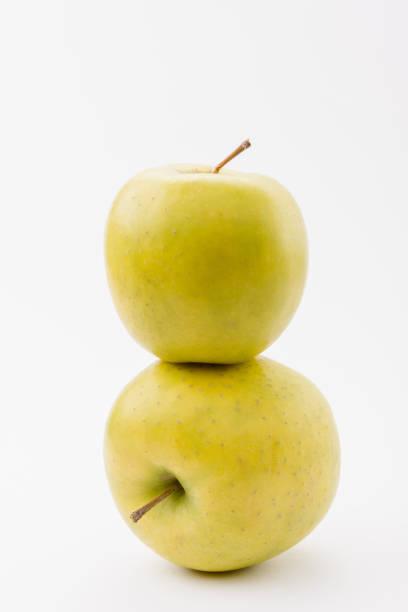 pile de deux pommes mûres de délicieux dorés sur fond blanc - golden photos et images de collection