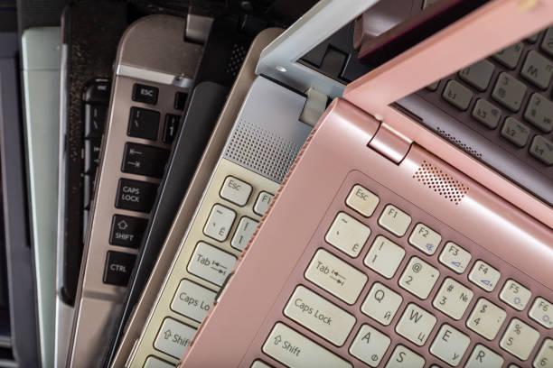 Stapel von gebrauchten Laptops in verschiedenen Farben und Modellen. – Foto
