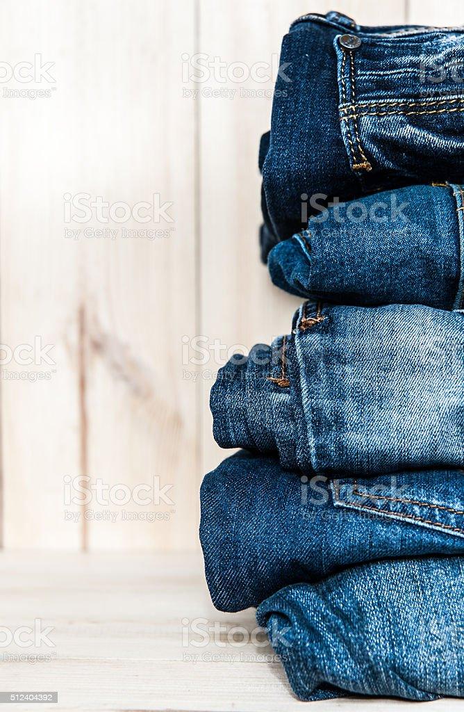 Stapel von verschiedenen Schattierungen blau Jeans auf hölzerner Hintergrund – Foto