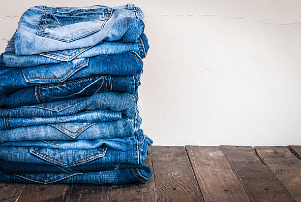 stack of various shades of blue jeans on old wood - jeans stock photos and pictures