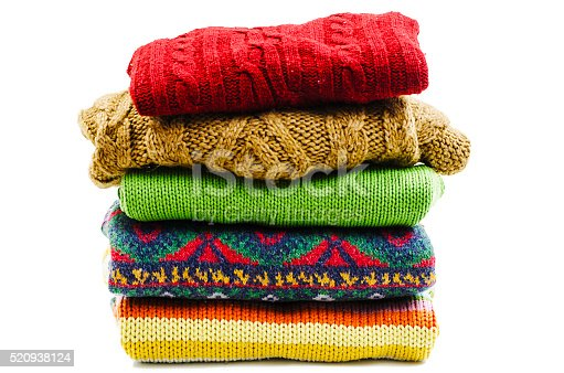Stack of various sweaters. Winter style. Isolated on white background