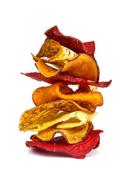 stack of vegetable chips isolated on white - gemüsechips stock-fotos und bilder