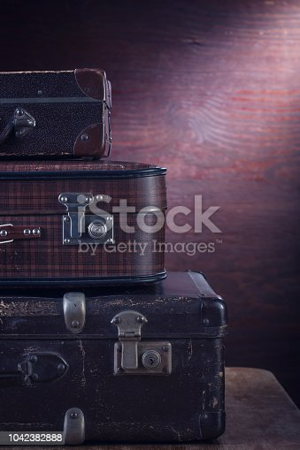 Vintage suitcases on wooden background.