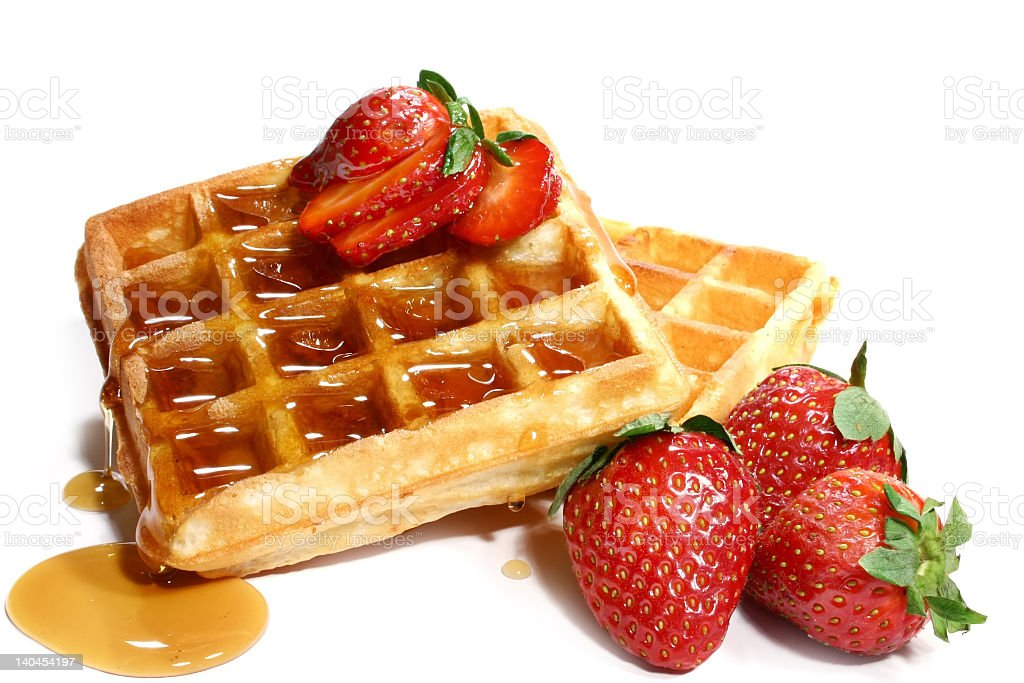 Stack of waffles with four strawberries and syrup stock photo