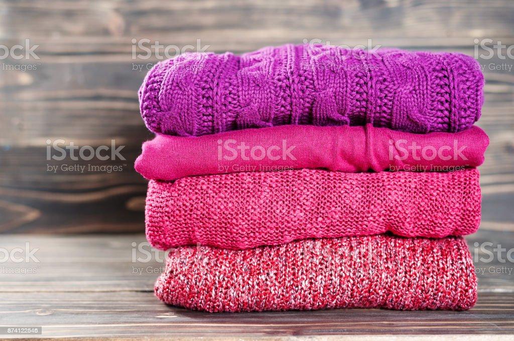 Stapel von warmer Strick-Kleidung auf einem Holztisch liegend – Foto