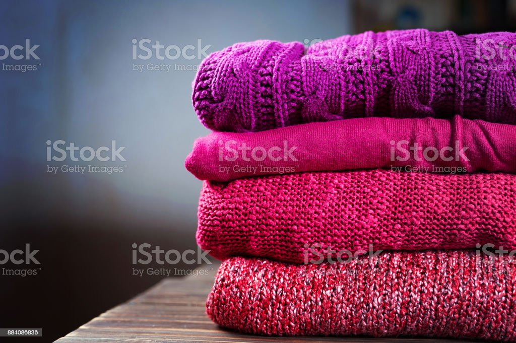 Stack of warm knitting clothing lying on a wooden table stock photo
