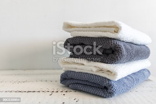 A stack of white and grey bath towels on white wooden table. Spa and wellness, cotton terry textile.