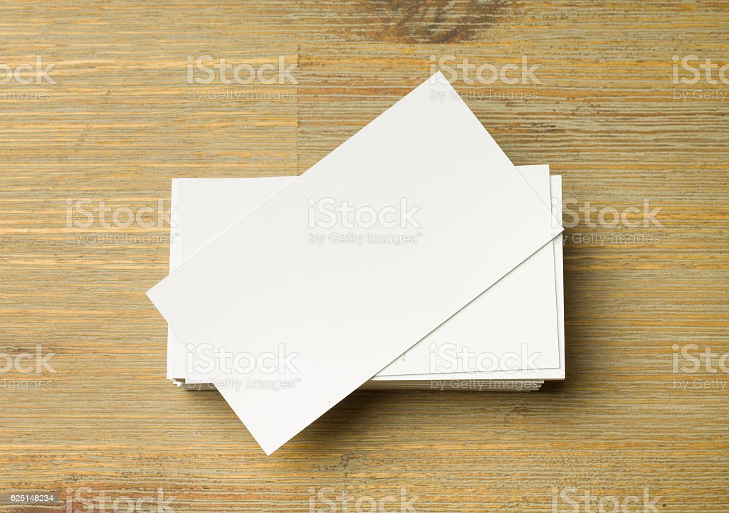 Stack of white not aligned business cards on a brown stock photo