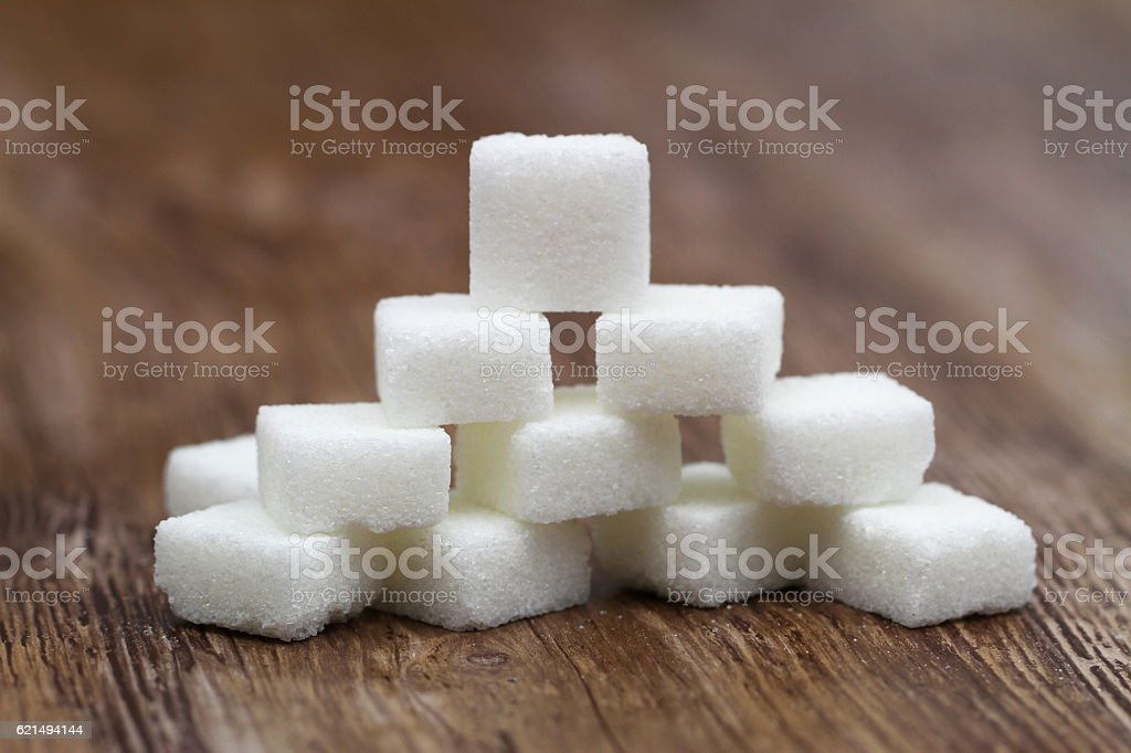 Stack of white sugar cubes on wooden surface foto stock royalty-free
