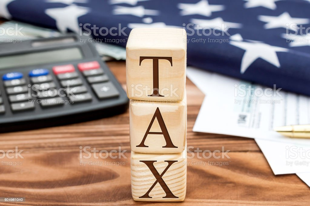 Stack of wooden cubes with word 'TAX' on the table with tax forms, american flag and calculator. Tax concept. stock photo