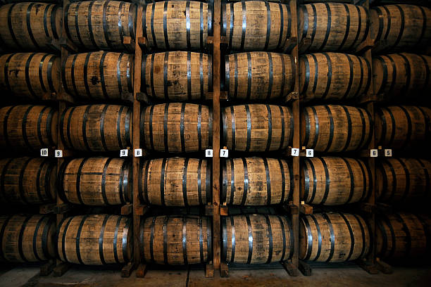 stack of wooden whiskey barrels - barrel stock pictures, royalty-free photos & images