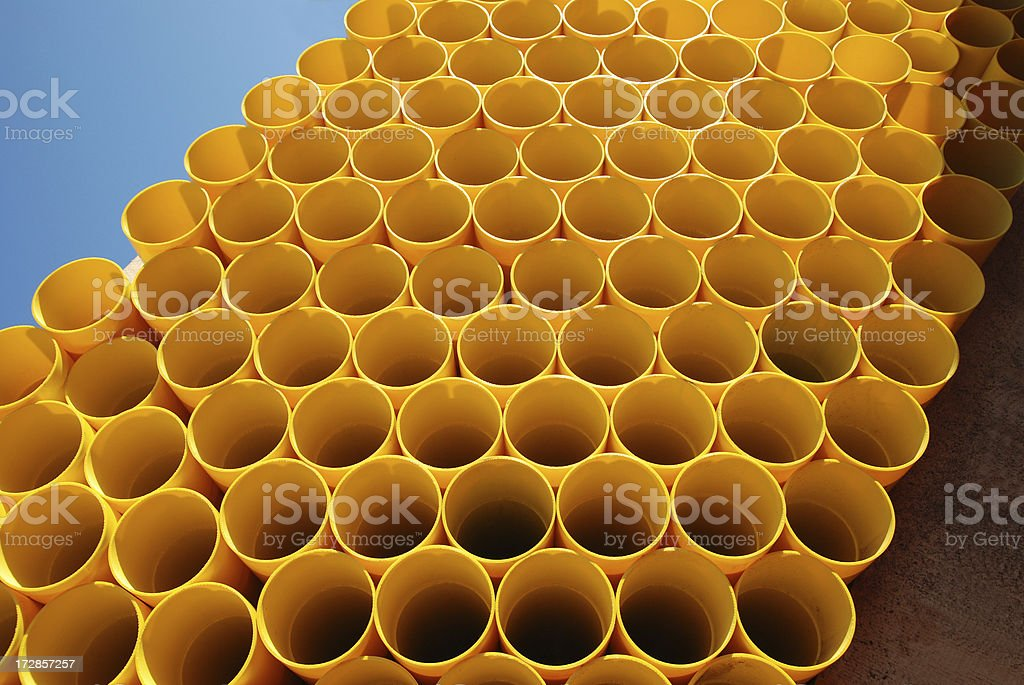 Stack of yellow plastic pipes stock photo