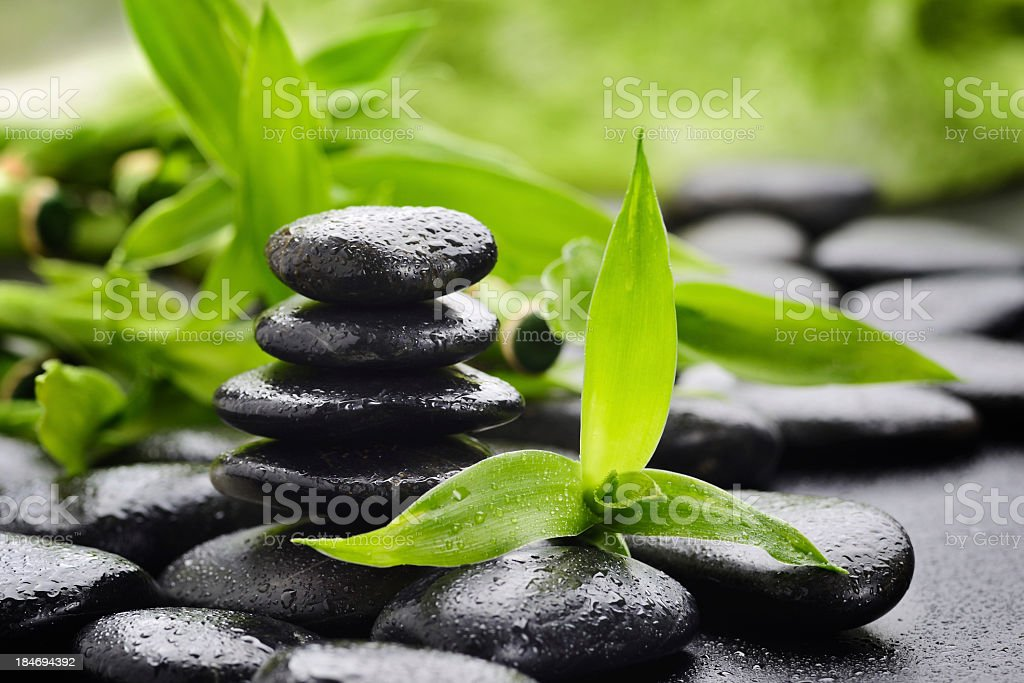 A stack of Zen stones and green leaves royalty-free stock photo