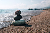 Stack of zen stones on beach near sea. Tower of spa rocks on sand at ocean. Balanced pebbles outdoors on sunny summer day. Oriental calm and harmony symbol. Wellness and tranquility concept