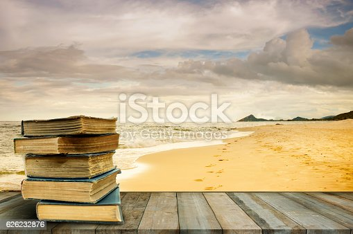 istock Stack old books on wood table at beach 626232876