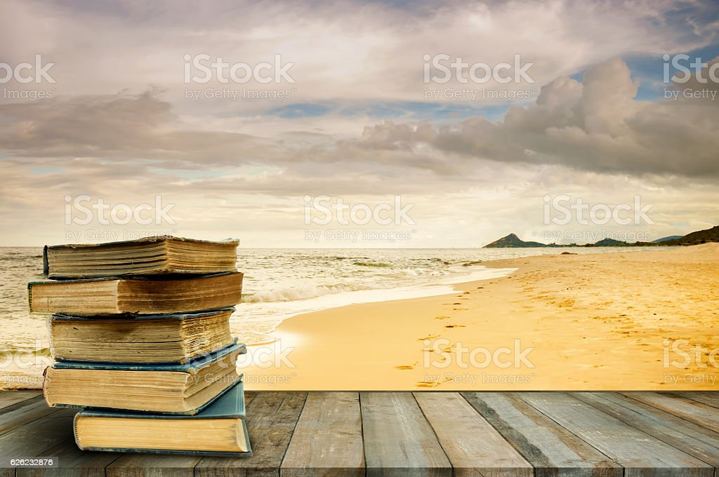Stack old books on wood table at beach stock photo