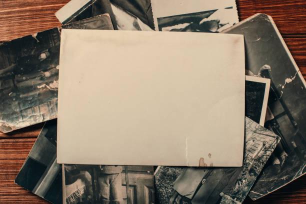 stapel oude foto's op tafel. mock-up blanco papier. ansichtkaart verkreukelde en dirty vintage. retro kaart - foto stockfoto's en -beelden