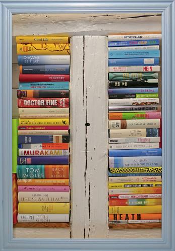 Stack ot books in blue wooden frame