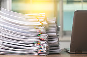 istock Stack overload document report paper with laptop computer for work from home , business concept of paperless used. 1216296628