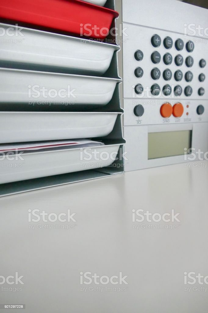 Stack pf silver and red colored stationery boxes with calculator on side stock photo