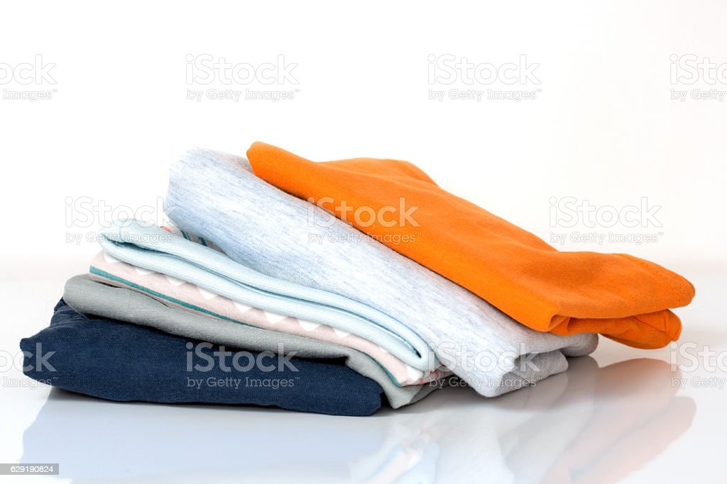 Stack pile folded cotton clothes on white. stock photo