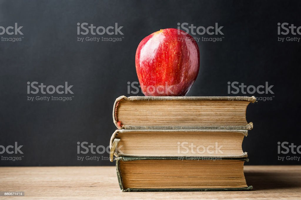 Stack Pile of Old Books Red Glossy Apple on Top. Learning Education Knowledge Concept. Blackboard Background. Classrom. Copy Space. Conceptual stock photo