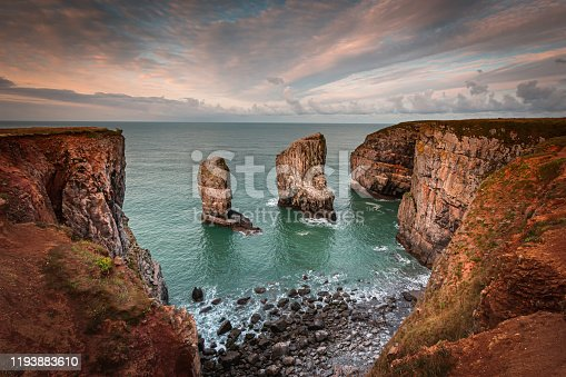 Stack rocks photographed at sunrise on dramatic coastline of Pembrokeshire ,South Wales,UK.Moody, colourful sky over bay with turquoise water, rock formation and cliffs lit by morning light.Tranquil seascape scene.
