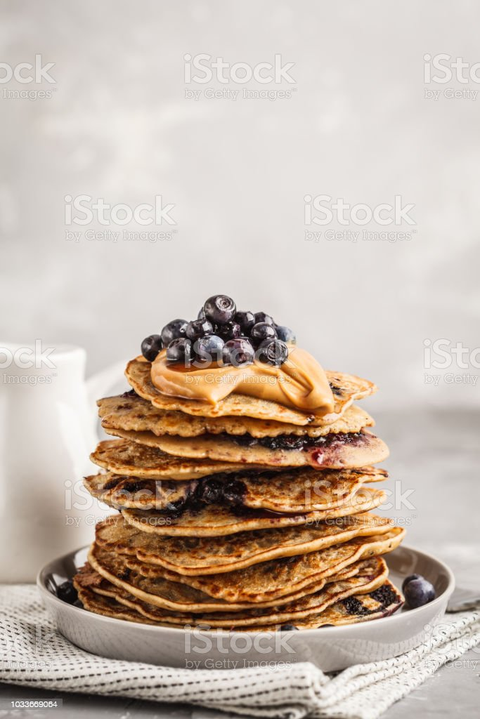 Stack vegan blueberry pancakes with peanut butter and syrup. stock photo