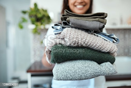 Closeup shot of a young woman holding a pile of folded laundry at home