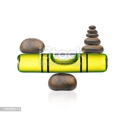 Isolated shot of stacked balancing stones with bubble level on white background.