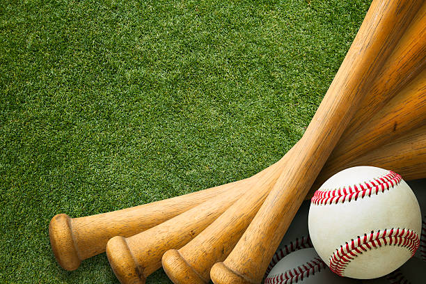 stacked baseball bats and ball on grass field - baseball bat stock photos and pictures