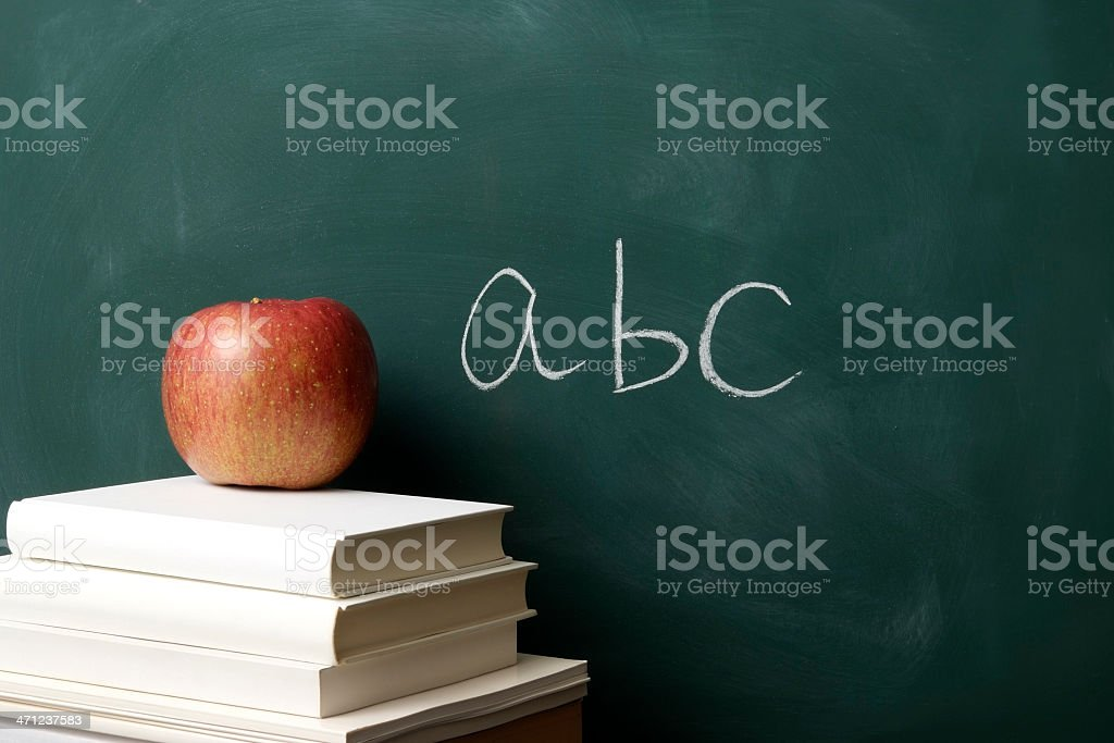 Stacked blank books with red apple against blackboard royalty-free stock photo