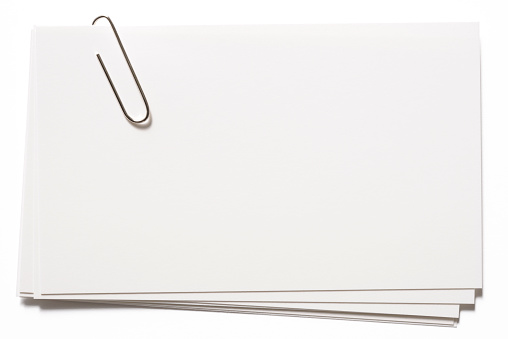 Stacked blank cards with a paper clip, isolated on white background with clipping path.