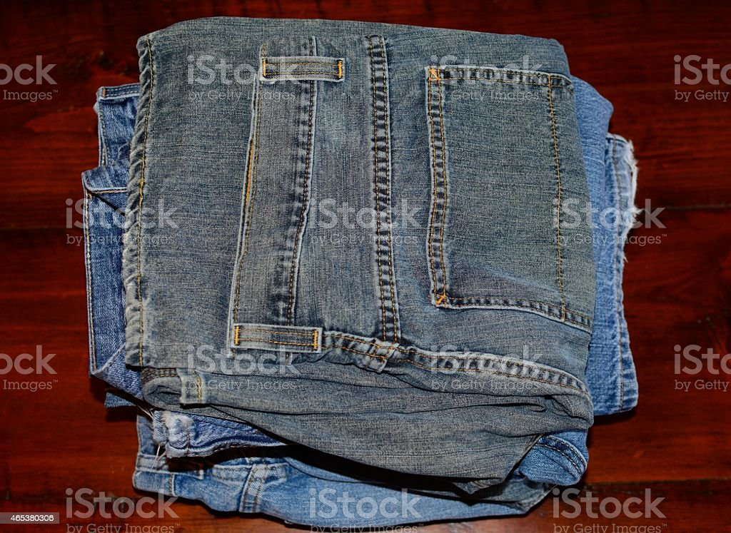 Stacked Blue Jeans on a Wooden Table stock photo
