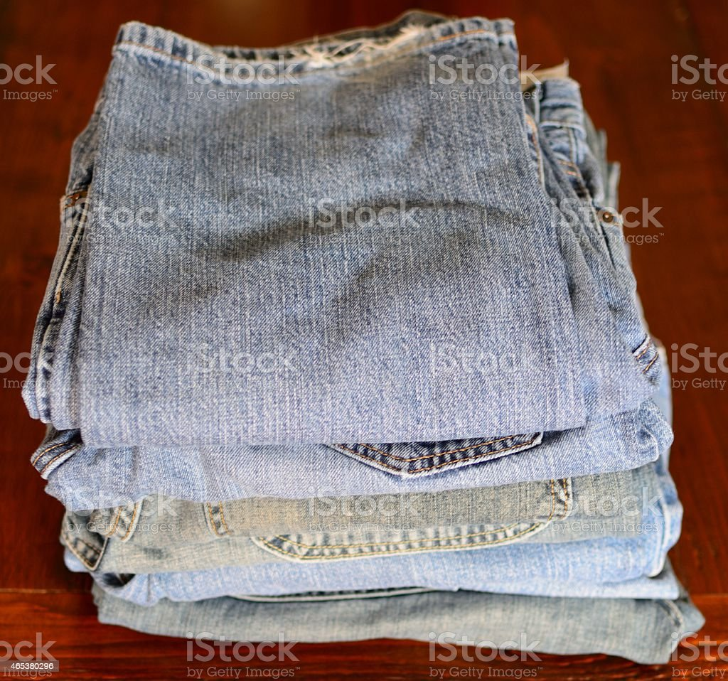 Stacked Blue Jeans on Wood stock photo