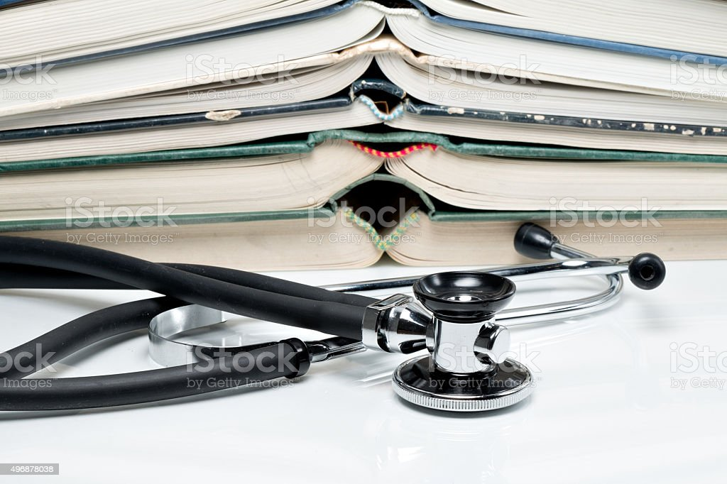 Stacked books with stethoscope stock photo