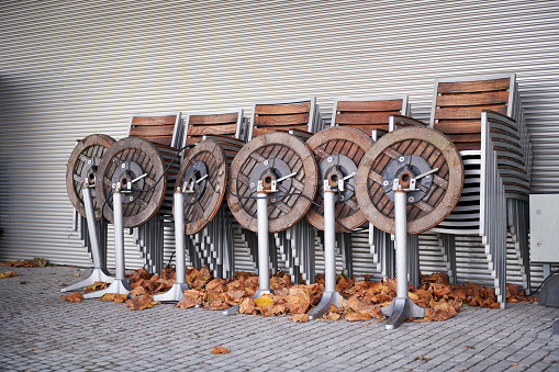 Stacked chairs of a corona closed sidewalk cafe in autumn