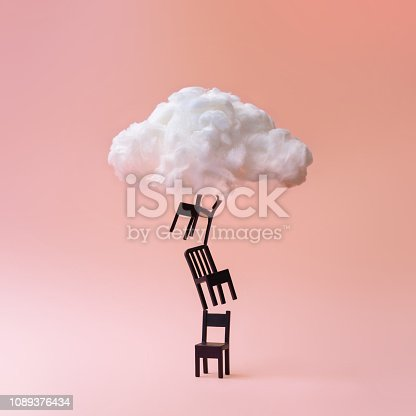 istock Stacked chairs with cloud against coral color background. 1089376434