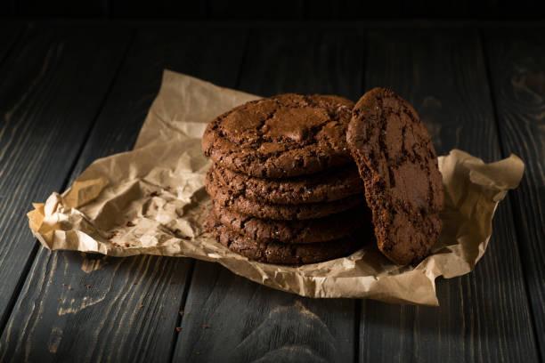 gestapelte schokoladenkekse auf kraftpapier - schokoladenplätzchen stock-fotos und bilder