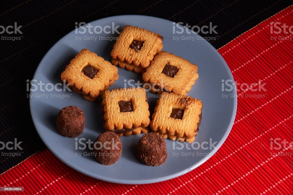 Stacked chocolate chip cookies on gray style plate on red and black wooden table - Royalty-free Baked Stock Photo