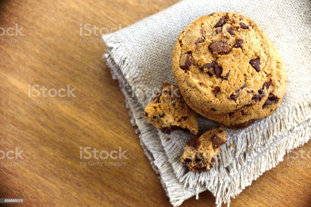 Stacked chocolate chip cookies on white napkin in country style stock photo