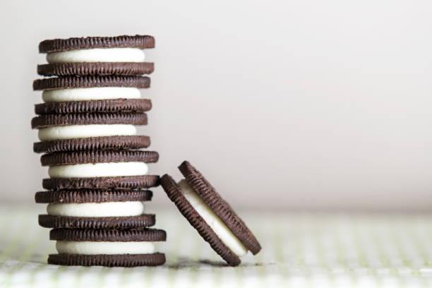 Empilhados os cookies de chocolate sanduíche contra um fundo branco - foto de acervo