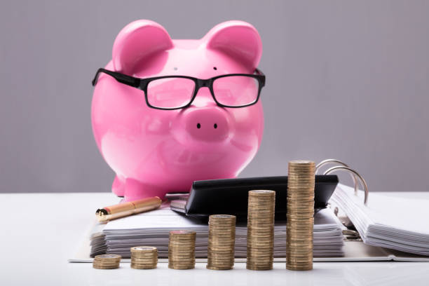 Stacked Coins And Document In Front Of Piggy Bank Close-up Of Stacked Coins And Document In Front Of Piggy Bank On Desk 40 kilometre stock pictures, royalty-free photos & images